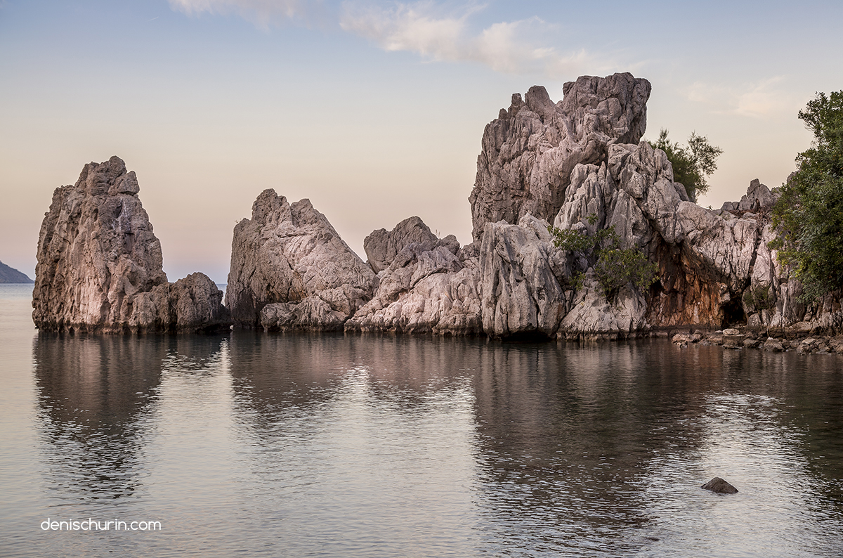 View of rocks with reflection in water in Cirali bay in Turkey at sunset